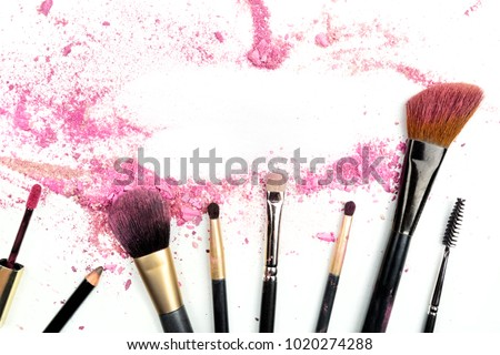 Traces of vibrant pink powder and blush forming a frame, with makeup brushes and lip gloss. A template for a makeup artist's business card or flyer design, with a place for text