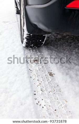 traces of winter tires in the snow on the pavement of a street