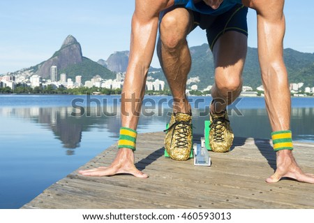 d4a670286d656d Track athlete with gold shoes crouching in starting blocks in front of the  Rio de Janeiro