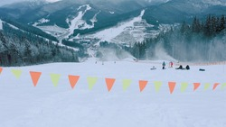 track border. safety flags on the ski slopes in the forested area in mountains, sport and leasure concept. Stock footage. Top view of tracks near trees and ski resort in winter season in 4K