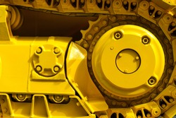 Track drive gear, bulldozer sprocket mechanism, large yellow construction machine with bolts, heavy industry, detail