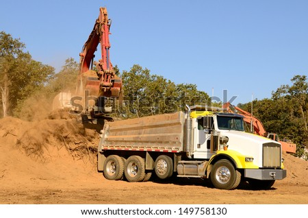 Track hoe excavator loading a 10-yard dump truck with dirt from a new commercial development construction project.
