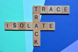 Track, Trace, Isolate, crossword in wooden alphabet letters isolated on blue