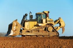 track-type bulldozer machine doing earthmoving work at sand quarry