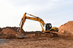 Track-type excavator during earthmoving works at open-pit mining. Heavy Construction Equipment Machines in Action. Digger during roadwork at construction site.