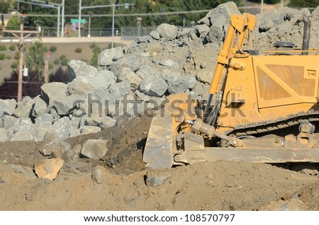 Tracked bulldozer working a rock pile at a large construction site removing a hill during an airport runway expansion project