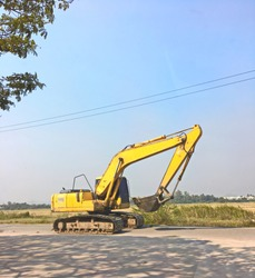 Tracked excavator, Trackhoe or Backhoe on a road construction site with blue sky background