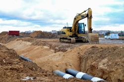 Tracked excavator working at a construction site during laying or replacement of underground storm sewer pipes. Installation of water main, sanitary sewer, storm drain systemsduring - Image