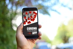 Tracking App concept for Corona virus with hand holding mobile phone with application design on screen in front of blurry outdoor background