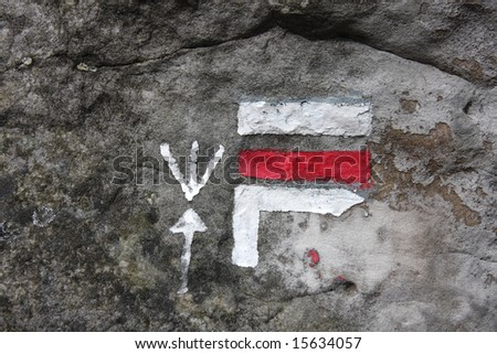 Tracking mark on a rock on a forest path in France