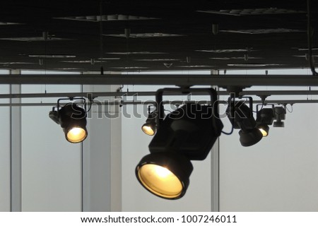 Tracking spotlights shines on the ceiling rail system #1007246011