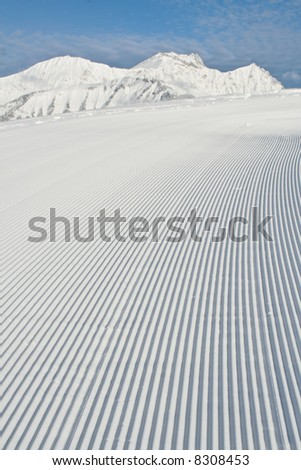 Tracks made by a snow grooming machine on a ski slope in the Alps.