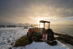Tractor at sunrise on an icy lake