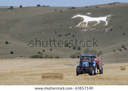 Tractor baling hay in field under White horse carved out of chalk hillside on Pewsey Downs at Alton near Avebury. Wiltshire. England. With heat haze.