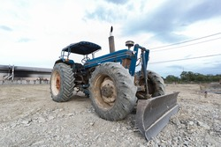 Tractor blue parked in a clearing in preparation for topsoil and beautiful blue sky in the background. The concept of a bulldozer prepares the topsoil for construction.
