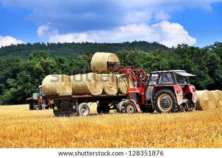 Tractor carrying hay at field in summer day