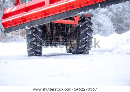 tractor cleans road from snow in the winter #1462270367