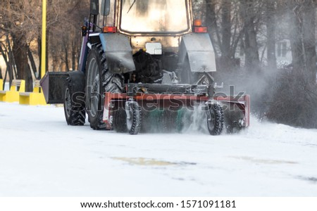 Tractor cleans the sidewalks of snow. Snow removal equipment. #1571091181