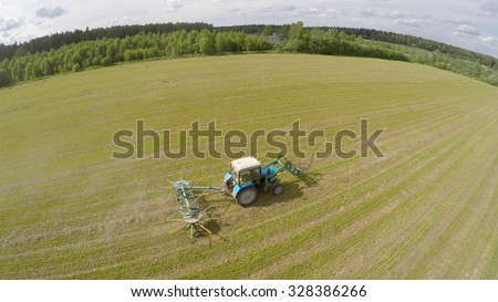 Tractor collect hay on field at summer sunny day. Aerial view videoframe