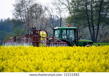Tractor crop spraying with fertilizer onto field