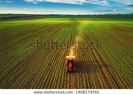Tractor cultivating field at spring, aerial top view #1408574960
