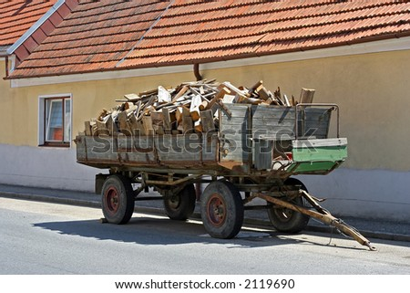 tractor-drawn trailer full with chunks of wood