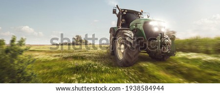 Tractor driving on a dirt road next to a field