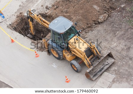 tractor excavator digging the ground to stop the leaking in water pipes