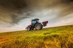 Tractor fertilize field before seeding