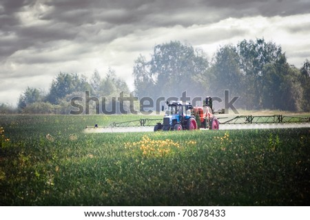 Tractor fertilizes crops in the field