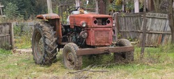Tractor in farm yard. Agricultural machinery and equipment.  Old rusty retro tractor in the yard of a rural farmer. Autumn rural landscape. Agriculture, industry and farming