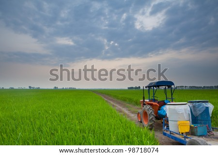 tractor in meadow green countryside on sunset
