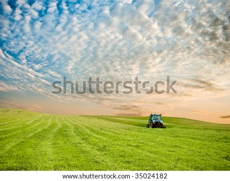 tractor in the field under sunset clouds - stock photo