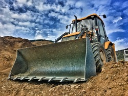 Tractor loader backhoe digger loader on a construction site with blue sky and dramatic clouds