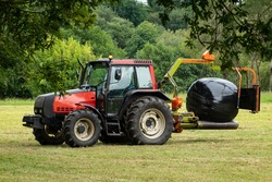 tractor making silo balls or wrapping grass on a tractor