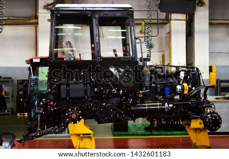 Tractor Manufacture work. Assembly line inside the agricultural machinery factory. Installation of parts on the tractor body - Image