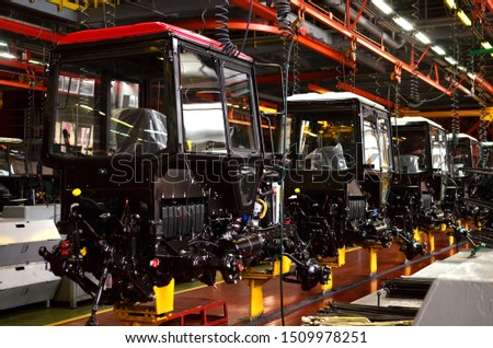 Tractor Manufacture works. Assembly line inside the agricultural machinery factory. Installation of parts on the tractor body. Tractor Manufacturing Facility. Tractors produced  #1509978251