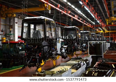 Tractor Manufacture works. Assembly line inside the agricultural machinery factory. Installation of parts on the tractor body. Tractor Manufacturing Facility. Tractors produced #1537791473