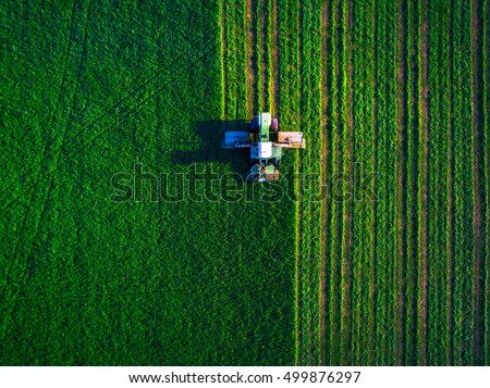 Tractor mowing green field, aerial view #499876297