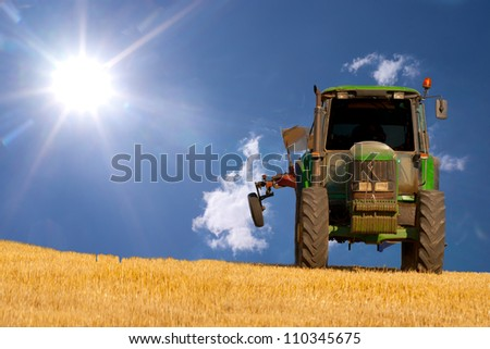 Tractor on a field with blue sky and sun as background