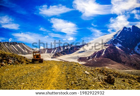 Tractor on a mountain road. Snowy mountain peaks landscape.  Tractor in mountains