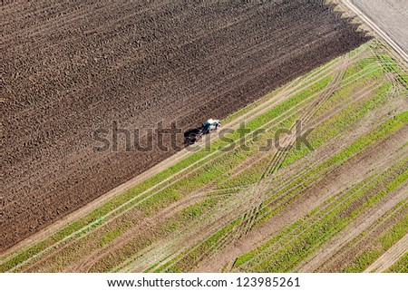 tractor on harvest field aerial view - stock photo