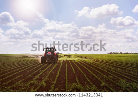 Tractor on soy field spraying