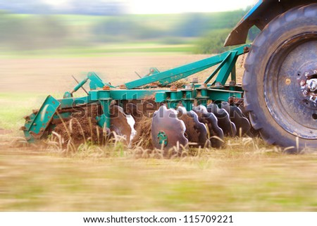 Tractor ploughing up the field. Motion blur was done for effect to emphasize speed