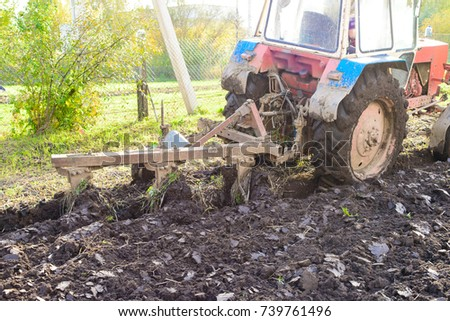 Tractor plowing a land, rural life in Russia. Concept of agriculture, farming, poverty and decline  #739761496