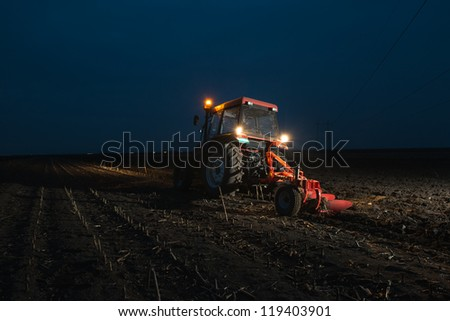 Tractor plowing at night