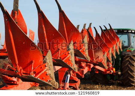 Tractor plowing field in sunny autumn day