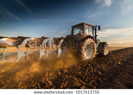 Tractor plowing fields -preparing land for sowing #1017613750