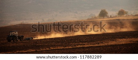 Tractor plowing the fields- golden sunrise panoramic view