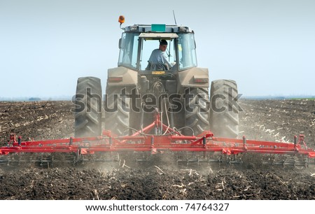 Tractor plowing the fields in spring